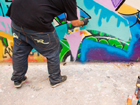 A sprayer, who doesn't like to be identified, sprays an unauthorized graffiti on a wall in Berlin. | Photo: © picture-alliance, Wolfram Steinberg