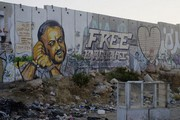 Garbage and resistance graffiti depicting the imprisoned Palestinian politician Marwan Barghouti on the so-called separation wall between the West Bank and Israel, near the Qalandia checkpoint. Photo: Stefan Weidner © Goethe-Institut