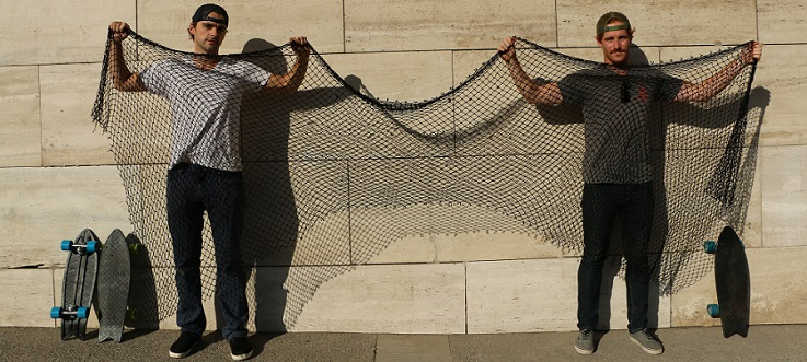 Ben Kneppers (left) and Kevin Ahearn hold up a fishing net to demonstrate how much net is needed to create their skateboards. Photo (CC BY-SA): Kevin Ahearn