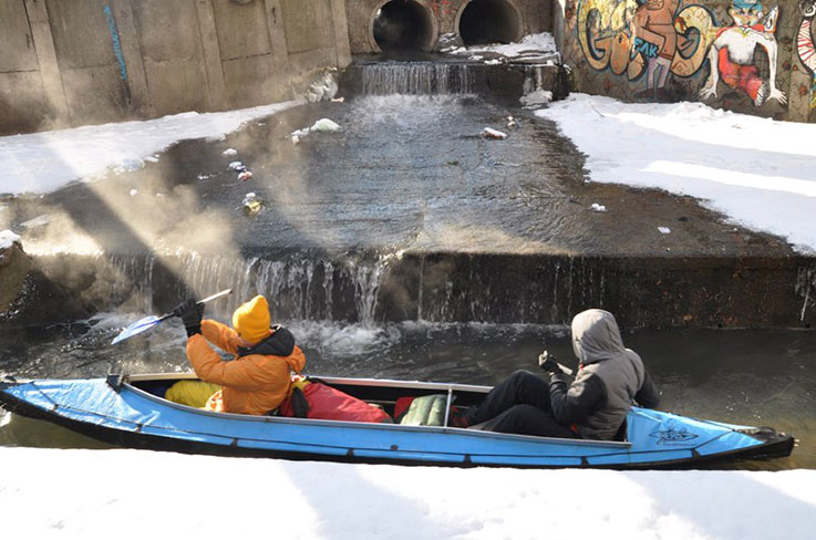 photo of a kayak in a narrow, urban channel