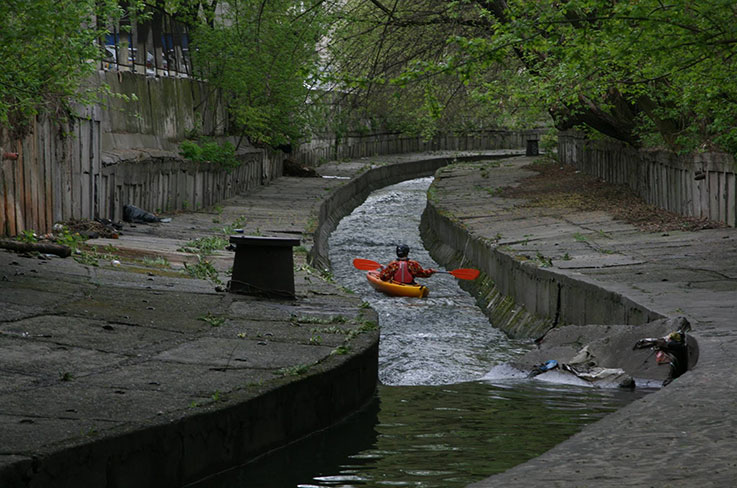 photo of a kayak in a narrow concrete channel