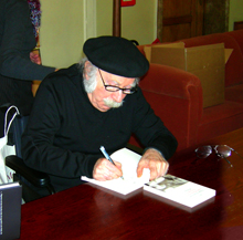 Edgar Hilsenrath is signing his book during his 80th birthday celebration, CC BY 2.5