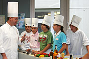Top cook Andreas Walker gives pupils instruction in tasting; Copyright: Eurotoques