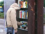 Homem apanha um livro nas 'Bibliotecas ao ar livre'; Copyright: Südpol-Redaktionsbüro Köster & Vierecke /S.Tenta