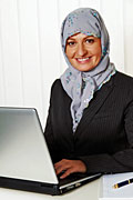 Muslim woman working at a PC; © Colourbox