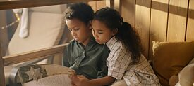 Two children read a book.