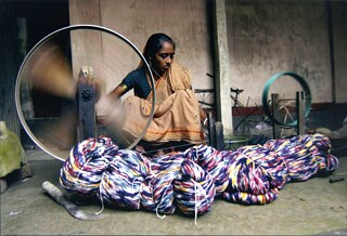Didi Bosak is spinning 100% cotton yarn for the preparation to weave cotton saris in Tangail. © Bibi Productions