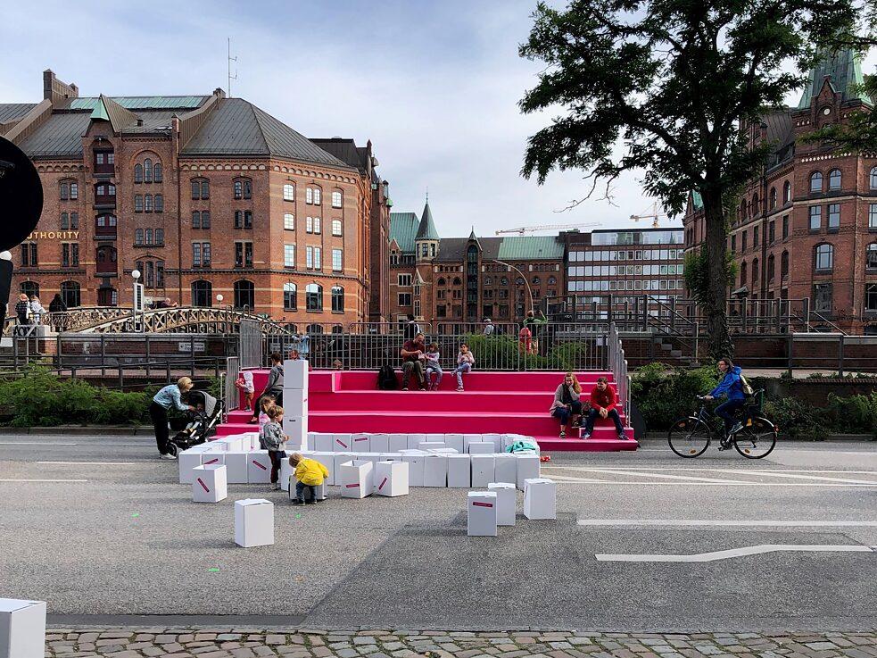 Spazio per andare in bici e giocare sottratto alle automobili: esperimenti reali come questo di Amburgo mostrano concretamente cosa può voler dire eliminare le auto dalla città.