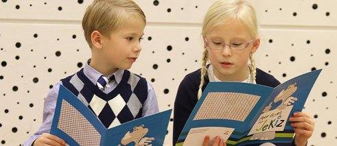 "Children reading the ""Jekiz""-flyer"