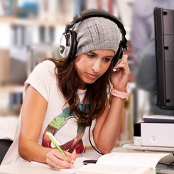 A young woman with headphones writing something down.