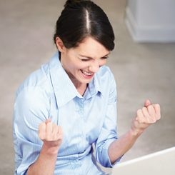 Excited businesswoman using laptop compute