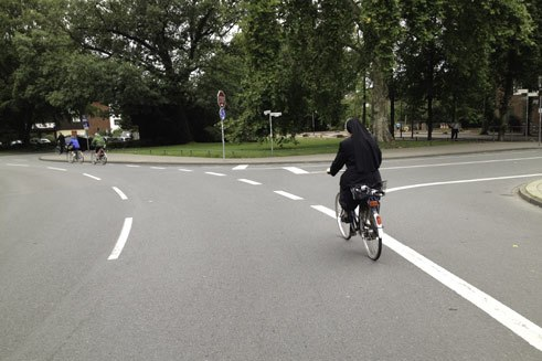 A nun cycling round a roundabout at Ludgeriplatz