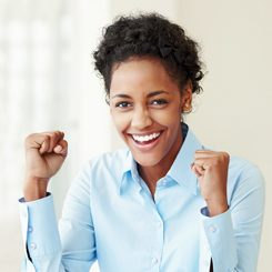 A young woman clenching her fists in joy.