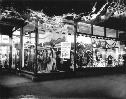 Shop Window, 816 7th Street NW, around 1907. The lights of these shop windows, perhaps readied for the holidays, entice you to consider a fur, a new suit (a steal, really, at $14.95), a new umbrella, or perhaps some 'Practical Presents for Little Folks'.