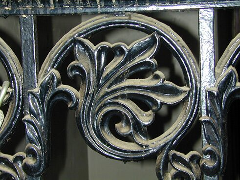 Dusty detail from a school stairway. Ironwork details in the school reveal the care with which Cluss decorated his buildings. (2000)