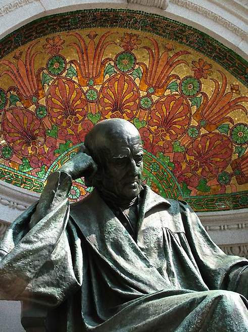Four large bronze bas-relief panels on the walls surrounding the statue depict Hahnemann as a student surrounded by books, a chemist in the laboratory, a teacher in the lecture room, and a physician at the bedside. Hahnemann is seated on a pedestal centered in front of a curving wall. The pedestal bears the well-known principle of homeopathy, expressed in the Latin phrase 'similia similibus curantur' (like cures the like). The words 'Die milde Macht ist gross' (gentle power is great) are carved on the base of the memorial. (2000)