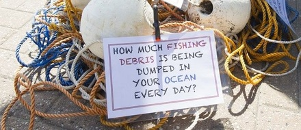 Sign with slogan: How much fishing debris is dumped in your ocean every day?