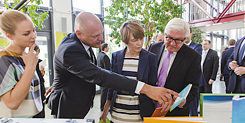 Johannes Ebert shows Frank-Walter Steinmeier and his wife information about the Goethe-Institut's activities for refugees