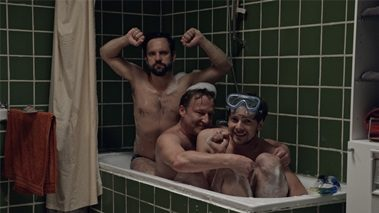 Three laughing men sitting in a bathtub.