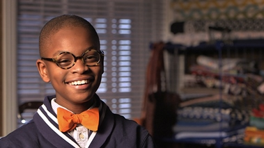 Young boy smiling into the camera. He is wearing a yellow bow tie.