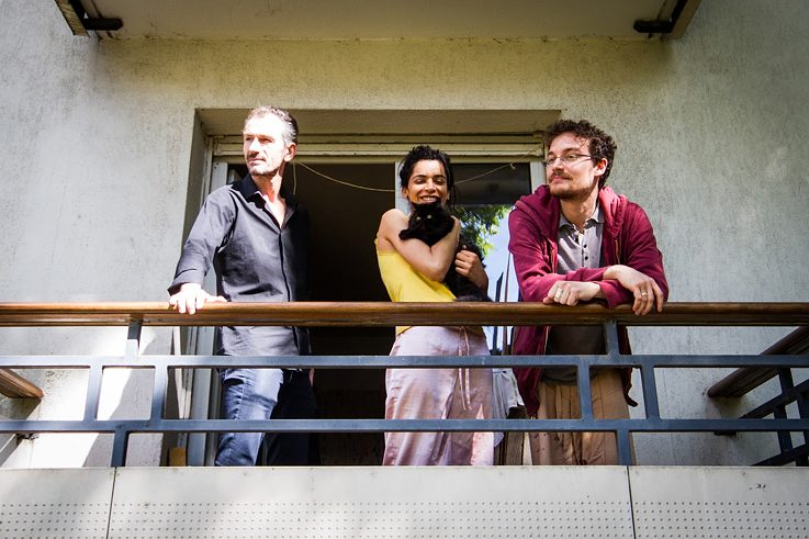 Zina Barrani (29), Toussaint Boos (30), students, and Samuel Ramirez, who sells paintings, on the balcony of their shared flat