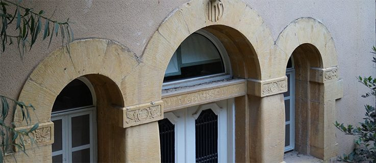 Keystone above the entrance to the former German parish house on campus of École Supérieure des Affaires