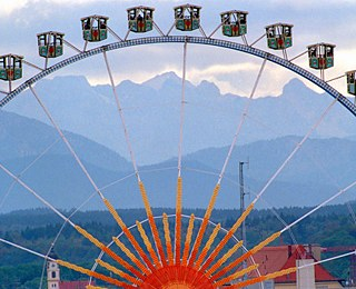 Munich Oktoberfest - Ferris wheel in front of alpine panorama