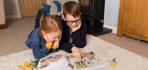 Boy and girl reading on carpet