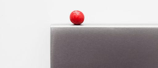 Boule rouge sur une plaque en acier gris