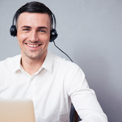 A smiling man with headphones looking up from his laptop.