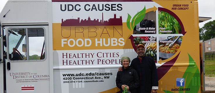 UDC president Ronald Mason and his wife Belinda DeCuir Mason pose in front of CAUSES Food Truck.