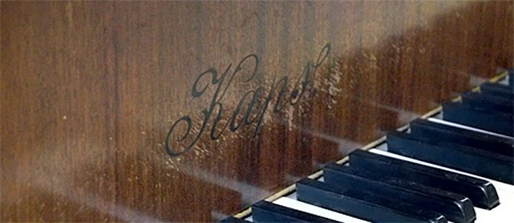 Keys and firm name on the front of the Kaps grand piano