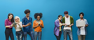 Young people of different nationalities looking at tablets, smartphones or laptops.