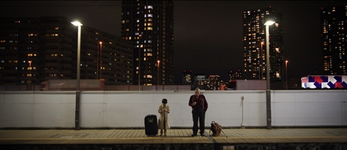 Big & Little, film still: a young boy and an old man stand waiting on a train station at night, there are high rise buildings in the background.