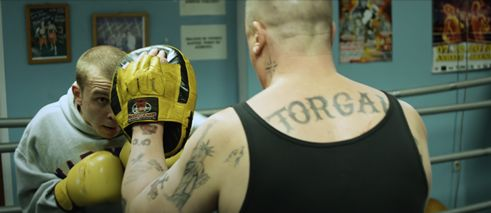 A Heavy Heart, film still: two men in a boxing ring, one of them is heavily tattooed