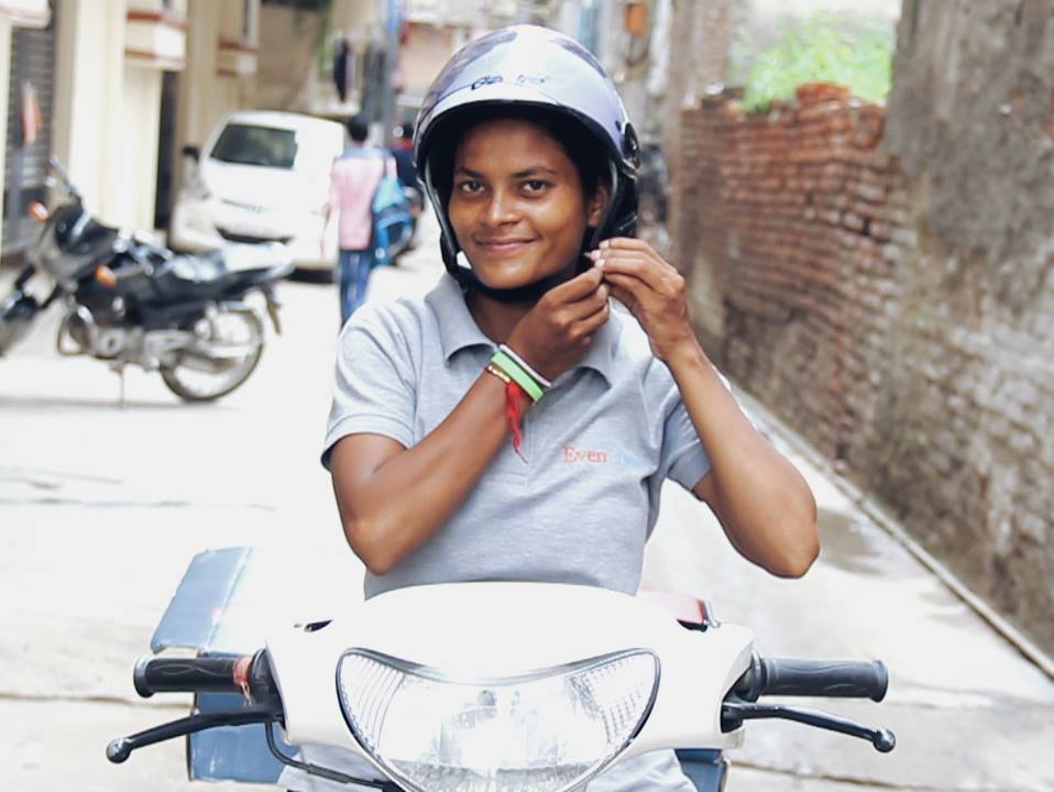 Helmet-wearing, scooter riding delivery girl Sunita