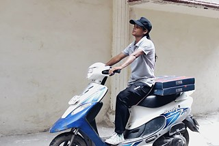 Sunita on her delivery scooter