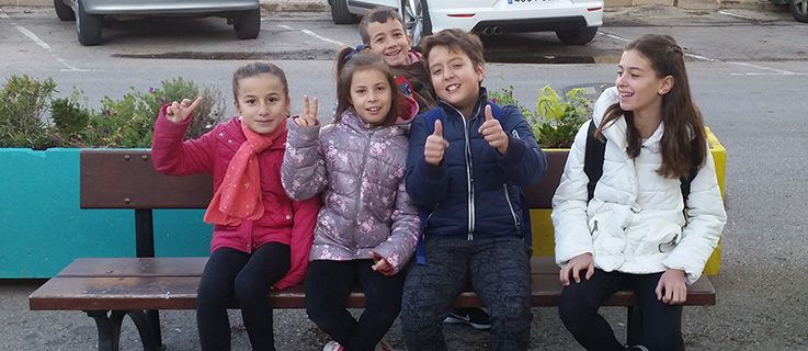 Nine-year-old Elena, with her fellow walkers, on a bench in front of their school.
