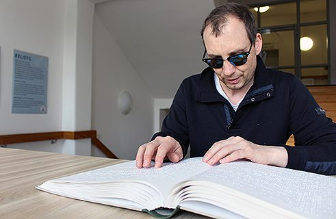 Stefan Debus reading a book in braille at the Central Library for the Blind.