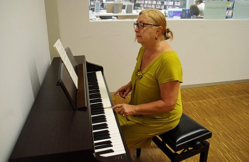 Renate uses the electric piano in the music room to find the right key for her choir pieces.