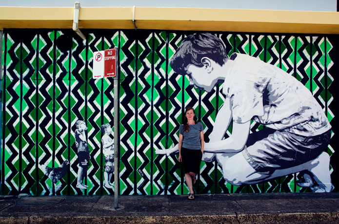The Street Art Artist Mandy Schöne-Salter in front of her work 'Imagine' (2015). This is a stencil and paste-up artwork created for the Avalon Art Carnival 2015. The work envisages the imaginary worlds children enter during playtime.