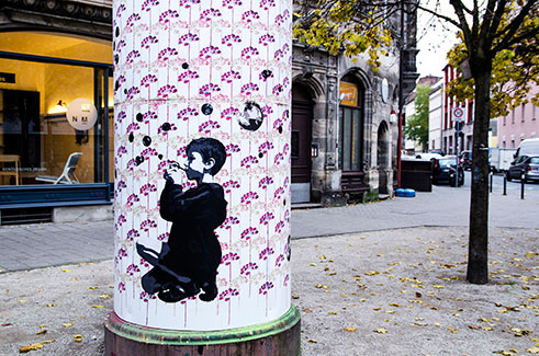Mandy Schöne-Salter designed and installed a street art mural for a round advertising pole in Nürnberg (Germany) called 'Litfaßsäule'. The mural consists of a two layered stencil as a background pattern and a couple of paste-up photographs on top.