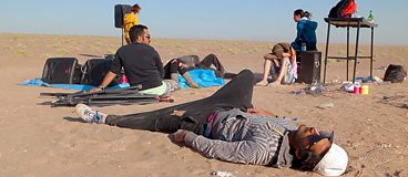 Film still: people laying and sitting in the sand