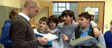 Film still: Teacher surrounded by his students in a classroom