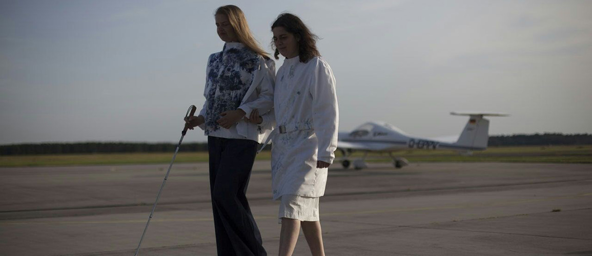 Two blind models walk on an airstrip in front of a glider. The blond women is guiding the dark-haired women who is holding her arm. The first is again wearing the squared poncho jacket, as well as a wide dark trouser blowing in the wind and dark sneakers. The other one wears the white coat which is now in better sight, it has now and then a blue pattern on the front and has knee-length. Underneath she wears a white skirt and white sneakers.