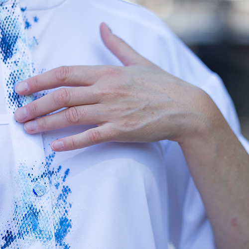Close up to the left part of the chest of a model standing outside wearing a white blouse with blue color around the buttons. The color goes from almost white to a dark blue, it is applied to the tissue in small dots and reminds of the shape of clouds. The model is softly touching the tissue.