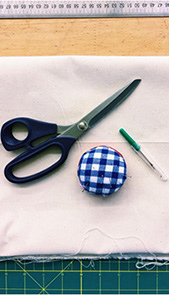 The pictures shows tailoring equipment lying on a white surface. Among the objects are a big scissor, a blue-white yarn and a sewing-needle with a green handle