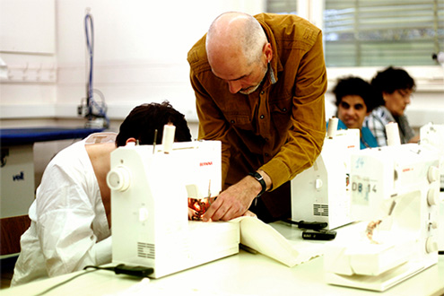 The picture shows two people, a partially impaired woman and a blind man using a sewing machine. The short-short haired woman is wearing a white blouse, while the bearded man is wearing an ochre-colored shirt.