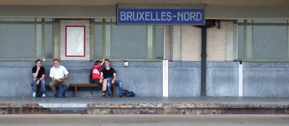 Two people sitting at the Brusells-North railway station