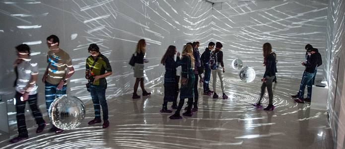 "Visitors illuminated by Mischa Kuball's light installation ""spacespeechspeed"" in Perm."